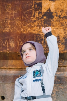 Dziewczyna w skafandrze przy ośniedziałą ścianą