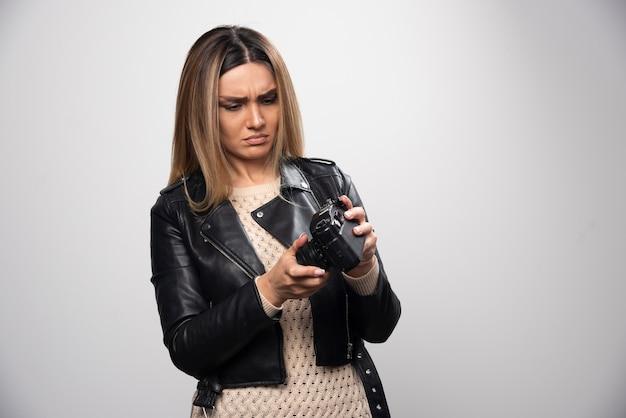 Dziewczyna w skórzanej kurtce sprawdza historię zdjęć w aparacie i wygląda na niezadowoloną