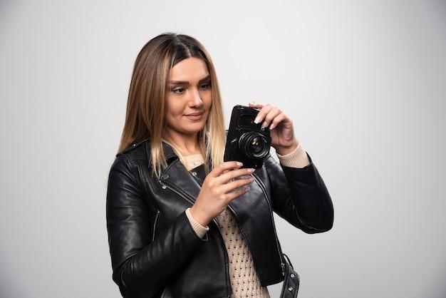 Dziewczyna w skórzanej kurtce sprawdzanie jej historii zdjęć w aparacie