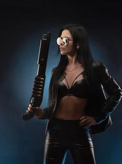 Dziewczyna w skórzanej kurtce ze strzelbą