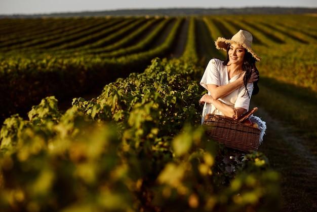 Dziewczyna w słomkowym kapeluszu iz wiklinowym koszem w słoneczny dzień spaceruje po polach porzeczki.