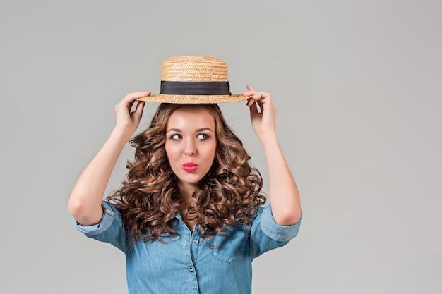Dziewczyna w słomkowym kapeluszu na szarej ścianie