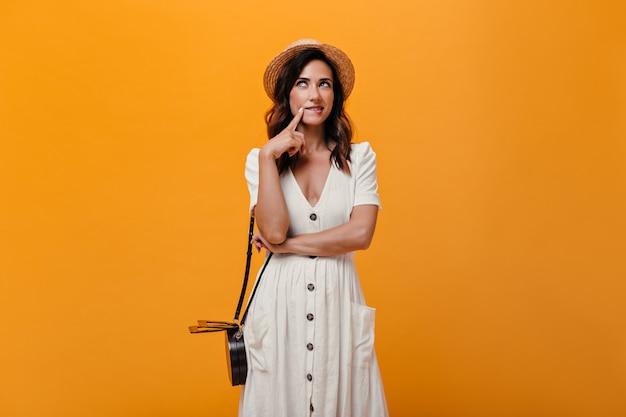 Dziewczyna w słomkowym kapeluszu pozowanie w zamyśleniu na pomarańczowym tle