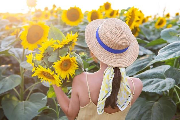 Dziewczyna w słomkowym kapeluszu stoi plecami i trzyma w rękach duży bukiet słoneczników na dużym polu słoneczników.