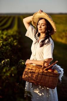 Dziewczyna w słomkowym kapeluszu trzymając kosz piknikowy z owocami. dziewczyna z zamkniętymi oczami z przyrodą na słonecznym polu porzeczki. pojęcie szczęścia, spokoju, miłości do życia.