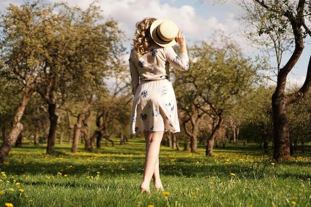 Dziewczyna w słomkowym kapeluszu w ogrodzie. widok z tyłu. modny casualowy strój na lato lub na wiosnę