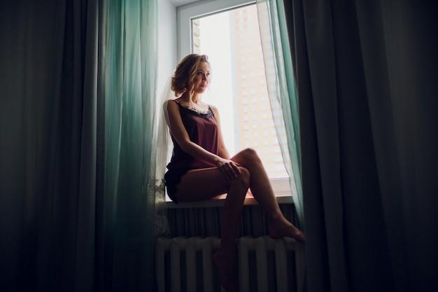 Dziewczyna w ślubnej zasłonie blisko okno w ciemnym pokoju