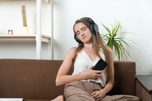 Dziewczyna w słuchawkach bezprzewodowych trzyma telefon w dłoniach, słuchanie muzyki i relaks.