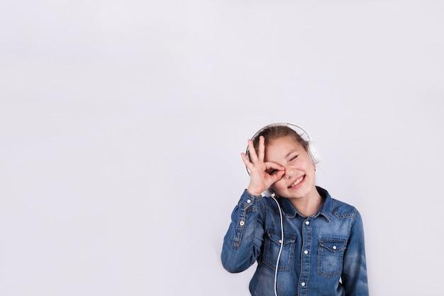 Dziewczyna w słuchawkach gestykulacji ok