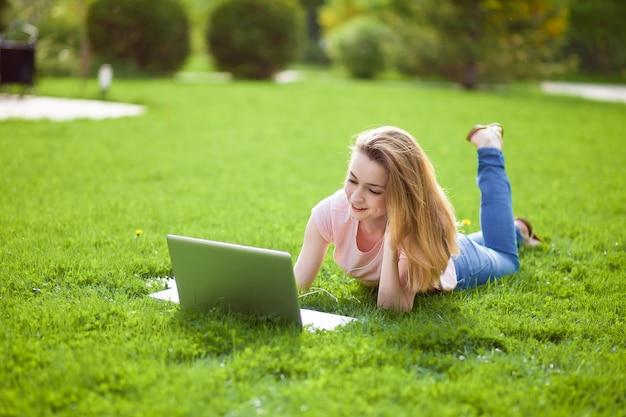 Dziewczyna w słuchawkach, leżąc na trawie z laptopem i uśmiechnięty