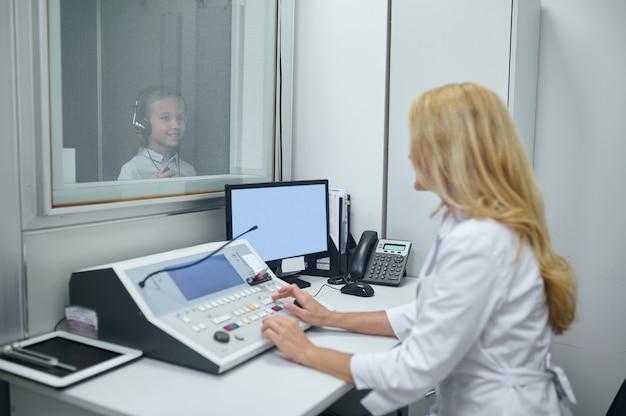 Dziewczyna w słuchawkach stojąca w dźwiękoszczelnej budce