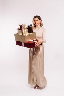 Dziewczyna w spódnicy i kurtce z wieloma prezentami w dłoniach na białym tle