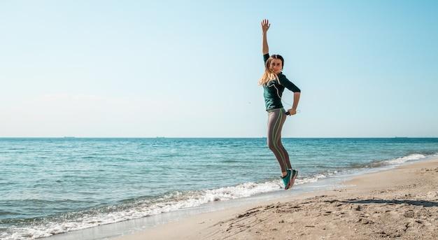 Dziewczyna w sportowej fitness nad morzem słuchania
