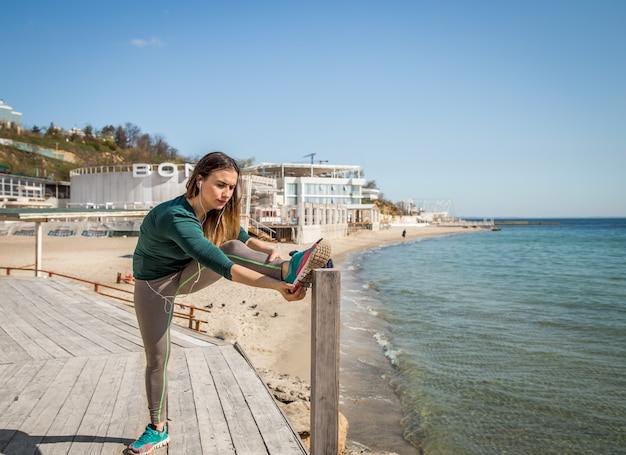 Dziewczyna w sportowej robi rozciąganie nad morzem