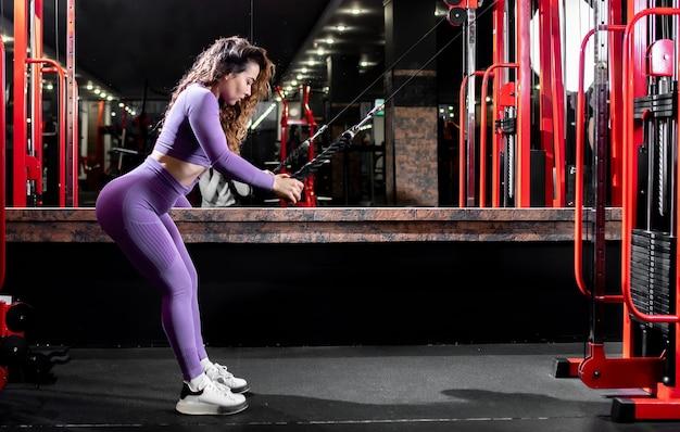 Dziewczyna w sportowej siłowni ćwiczy ze sprzętem fitness. pojęcie zdrowego stylu życia