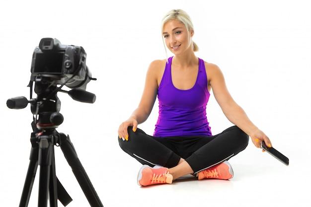 Dziewczyna w sportowym mundurze siedzi przed kamerą