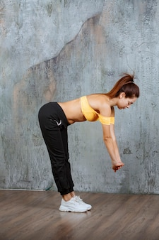 Dziewczyna w sportowym sprzęcie robi ćwiczenia rozciągające.