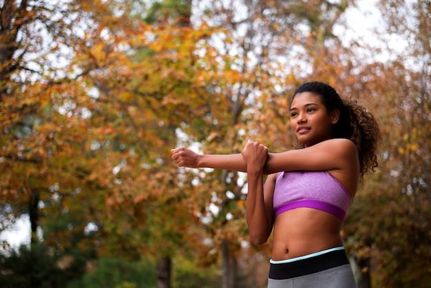 Dziewczyna w sportowym staniku robi rozciągania ćwiczeniu.