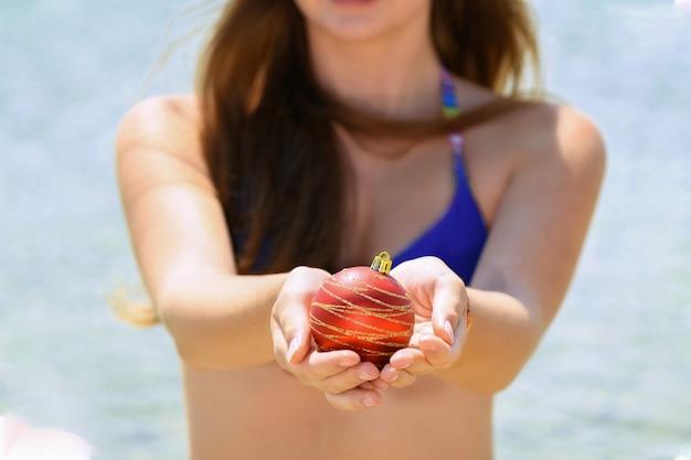 Dziewczyna w stroju kąpielowym, trzymając czerwoną bombkę na tle morza, święta bożego narodzenia