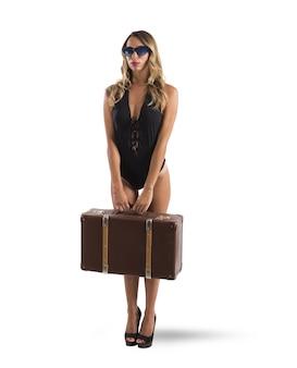 Dziewczyna w stroju kąpielowym z obcasami i walizką