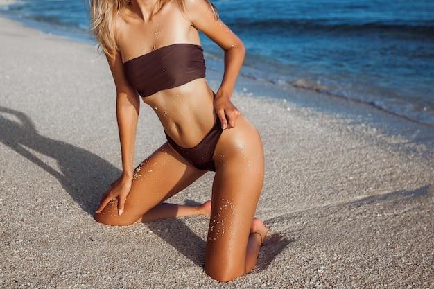 Dziewczyna w stroju kąpielowym z pięknymi nogami, opaloną skórą i seksownym tyłkiem, siedząca na plaży