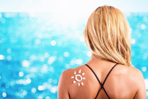 Dziewczyna w stroju kąpielowym ze słońcem z filtrem przeciwsłonecznym