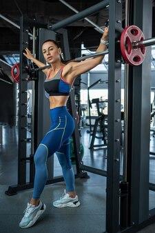 Dziewczyna w stroju sportowym stojąca w pobliżu kowala na siłowni
