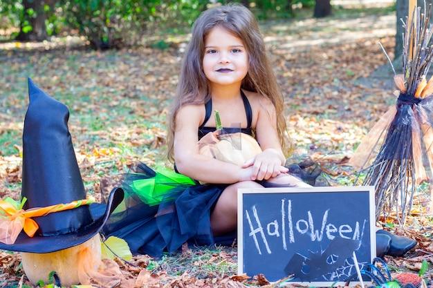 Dziewczyna w stroju wiedźmy na święta halloween. tabliczka z napisem: halloween. dziewczyna siedzi na trawie