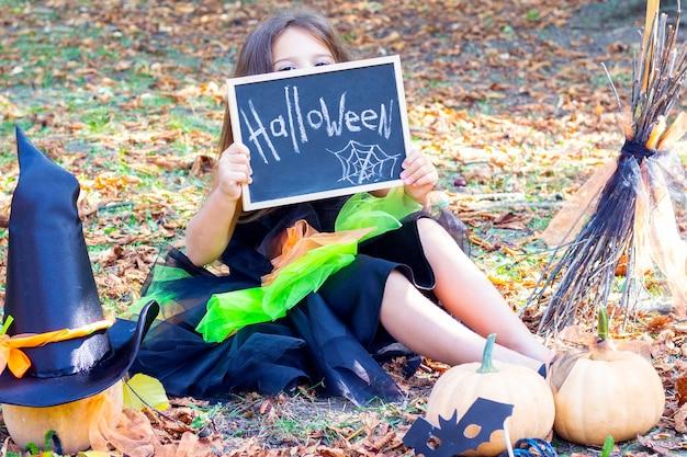 Dziewczyna w stroju wiedźmy na święta halloween. tabliczka z napisem: halloween. szczęśliwa dziewczyna siedzi na trawie i zamyka oczy znakiem