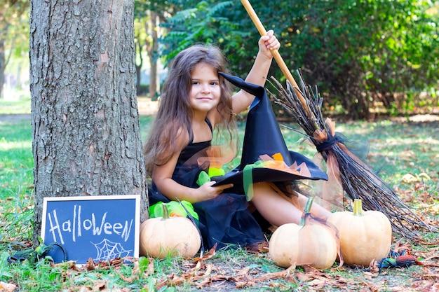Dziewczyna w stroju wiedźmy na święta halloween. tabliczka z napisem: halloween. szczęśliwa dziewczyna siedzi z miotłą