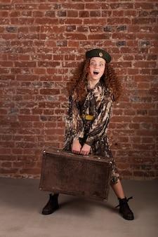 Dziewczyna w stroju wojska w ręku z walizką