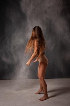 Dziewczyna w studio na szarym bez twarzy, cofa się