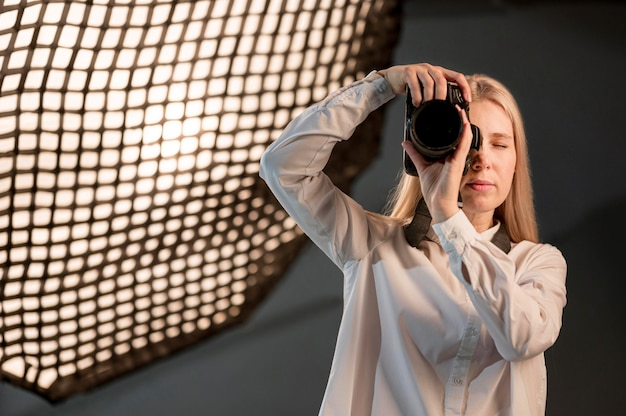 Dziewczyna w studiu bierze fotografię z kamerą