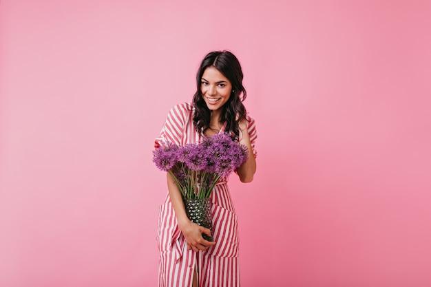 Dziewczyna w stylowej różowej sukience midi wygląda przyjaźnie, pozując z naręczem kwiatów do portretu w pomieszczeniach.