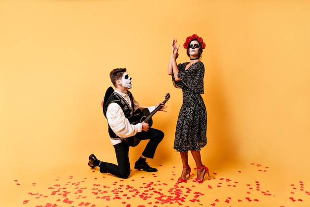 Dziewczyna w stylowej sukience z różami we włosach tańczy taniec hiszpański przy dźwiękach gitary. młody mężczyzna klęczy na jednym kolanie i śpiewa piosenkę swojej ukochanej kobiecie