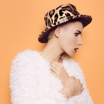 Dziewczyna w stylowym kapeluszu i płaszczu lamparta. seksowny nadruk
