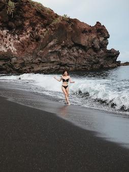 Dziewczyna w stylowym stroju kąpielowym ma odpoczynek na plaży
