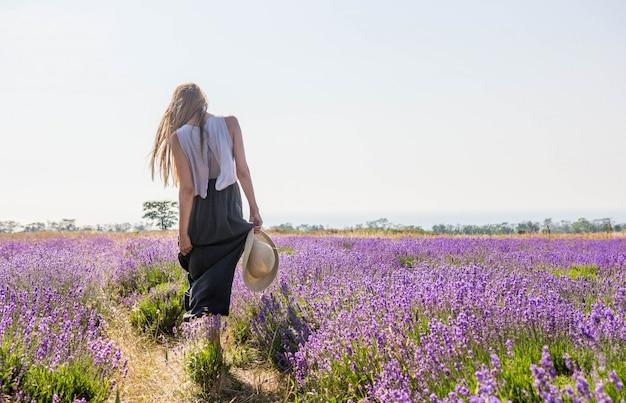 Dziewczyna w sukience chodząca po lawendowym polu z kapeluszem w dłoni