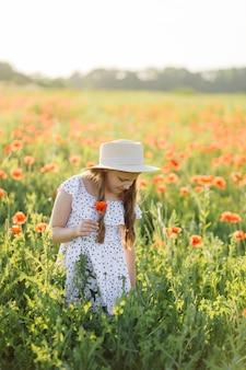Dziewczyna w sukience i kapeluszu stoi na polu