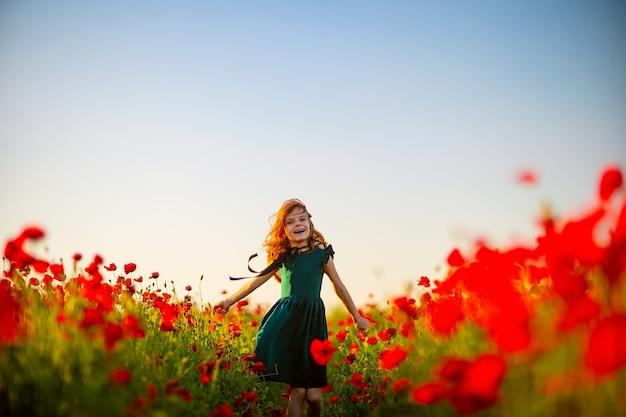 Dziewczyna w sukience i słomkowy kapelusz na zewnątrz w pole maku