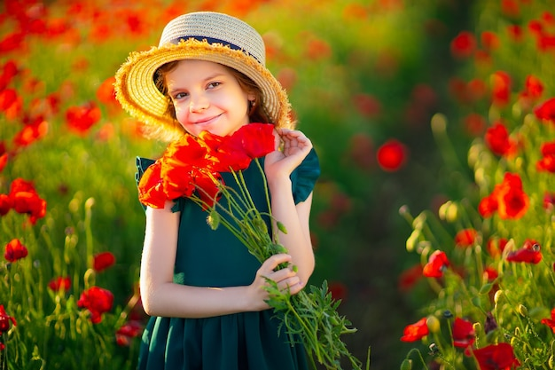 Dziewczyna w sukience i słomkowym kapeluszu na zewnątrz w polu maku