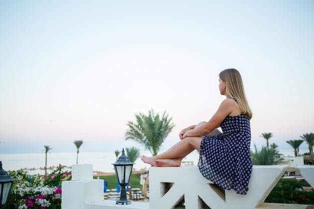 Dziewczyna w sukience na tle zachodu słońca i morza