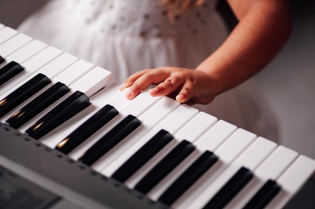 Dziewczyna w sukience naciska palce na klawisze syntezatora elektronicznego