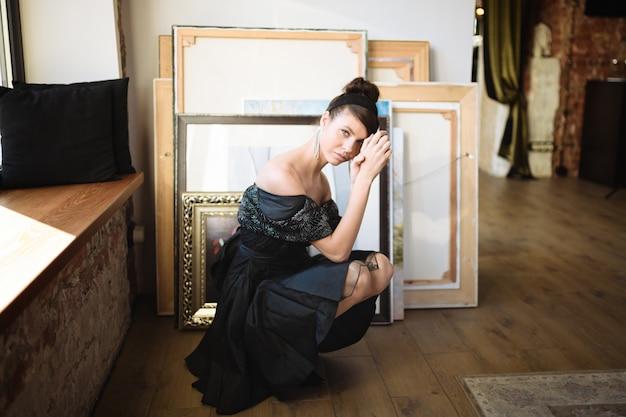 Dziewczyna w sukience siedzi obok obrazów