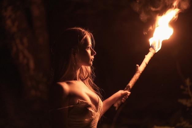 Dziewczyna w sukience w ciemnym lesie. w dłoni trzyma pochodnię