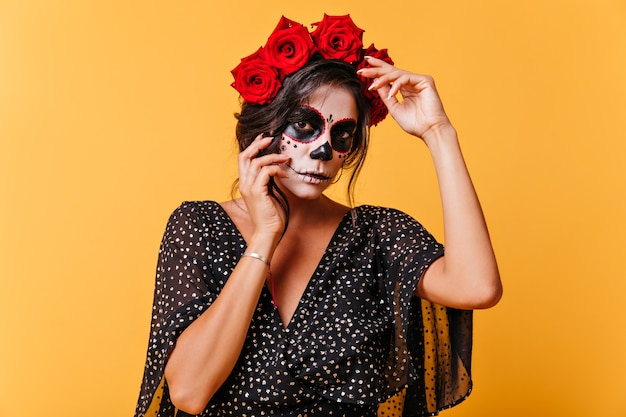 Dziewczyna w sukience z dekoltem w szpic i szerokimi rękawami pozuje do portretu na odizolowanej ścianie. meksykańska dziewczyna z różami na głowie