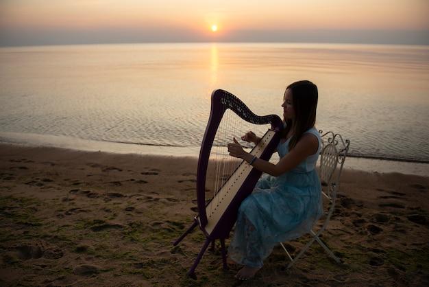 Dziewczyna w sukience z kwiatami bawi się na harfie celtyckiej nad morzem o zachodzie słońca