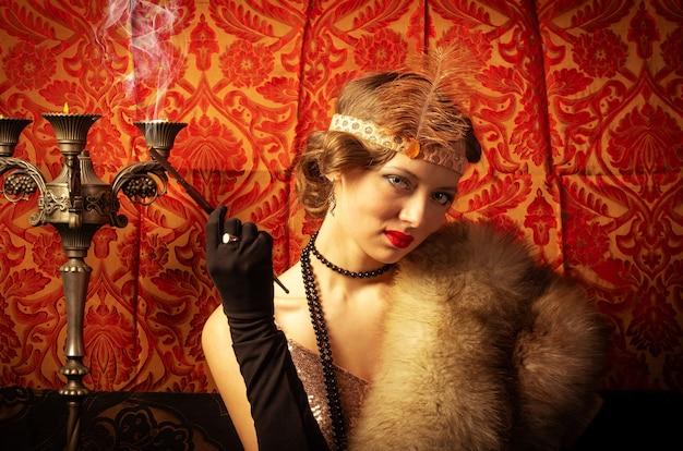 Dziewczyna w sukni wieczorowej z papierosem. studio fotograficzne w stylu retro