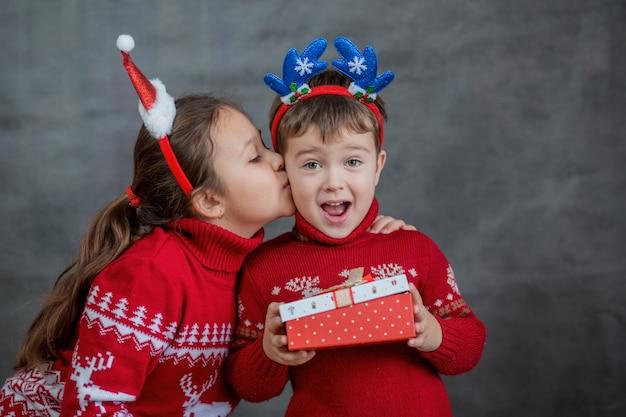 Dziewczyna w sweter boże narodzenie całuje chłopiec w sweter boże narodzenie z małym prezentem świątecznym.