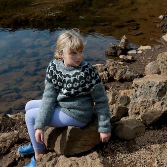 Dziewczyna w sweter siedzi na skałach przez lakeshore